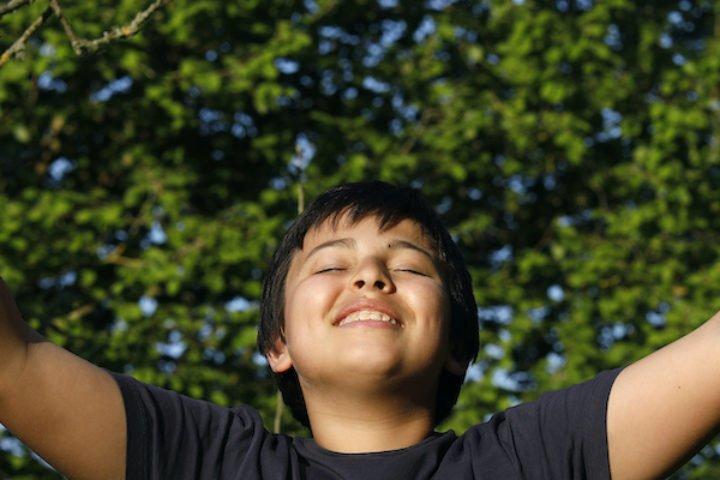 Garçon souriant à bras ouverts dans l'Eure, France.